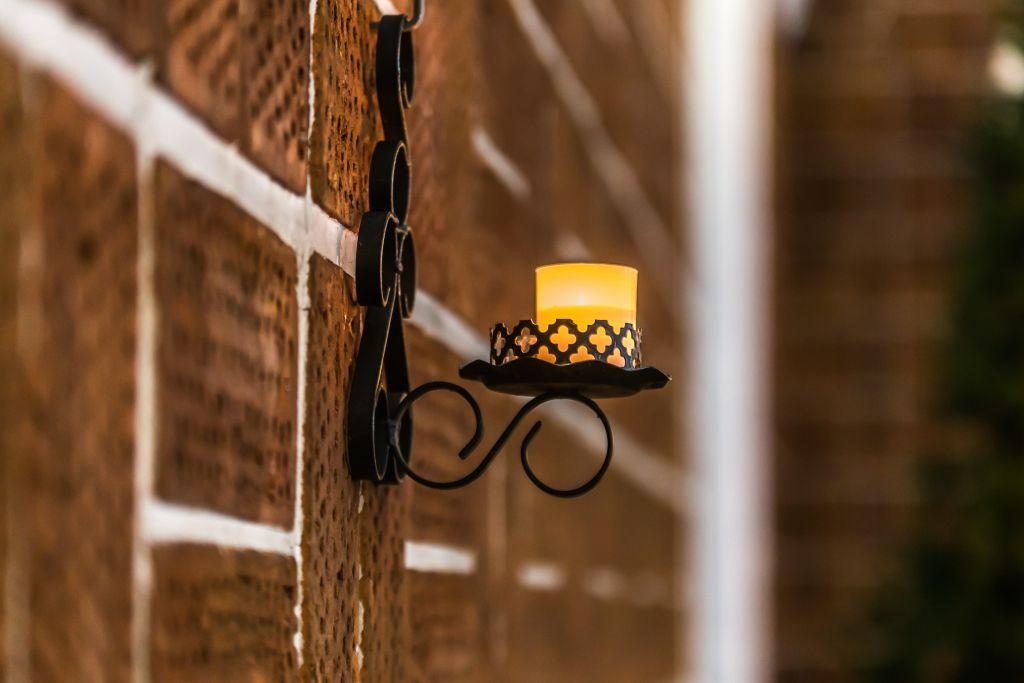 Palava kynttilä seinälampetissa